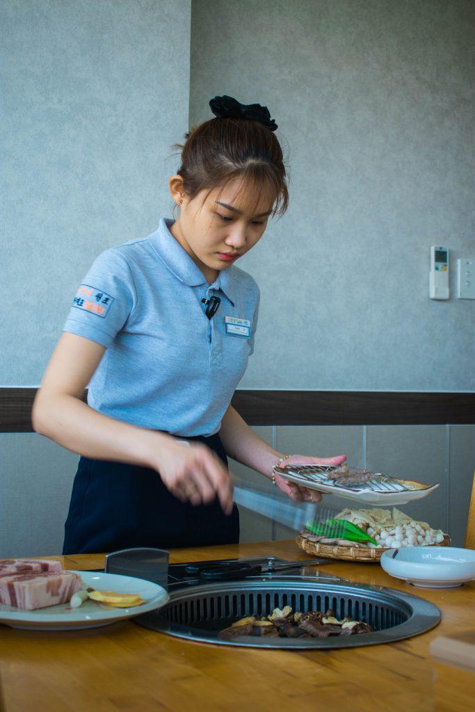 a waitress serving up Korean BBQ