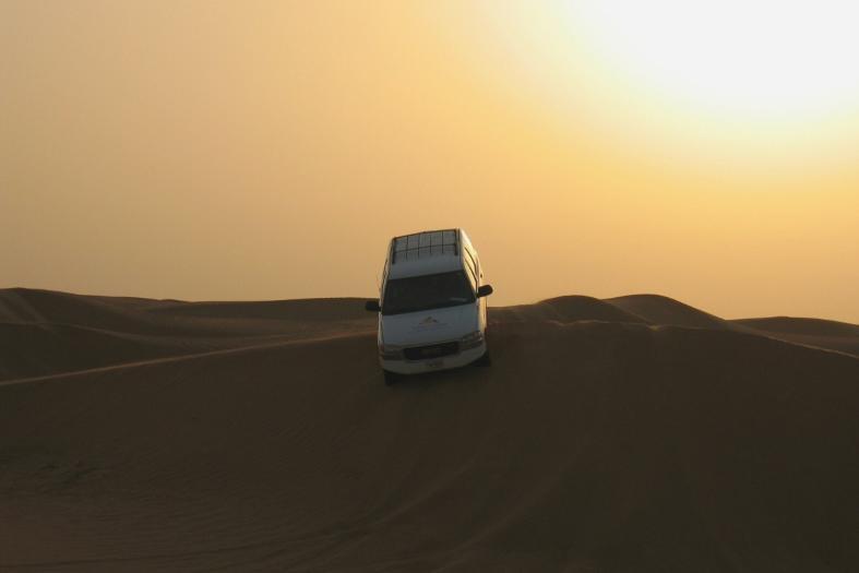 Cra driving over sand dunes in desert near Dubai
