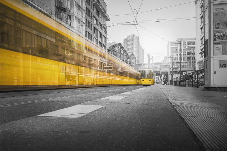 A yellow tram travelling through Alexanderplatz in Berlin